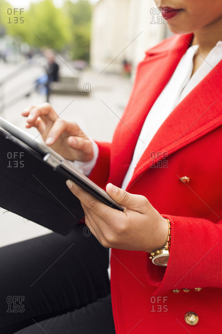 Woman in red jacket sitting outside using tablet
