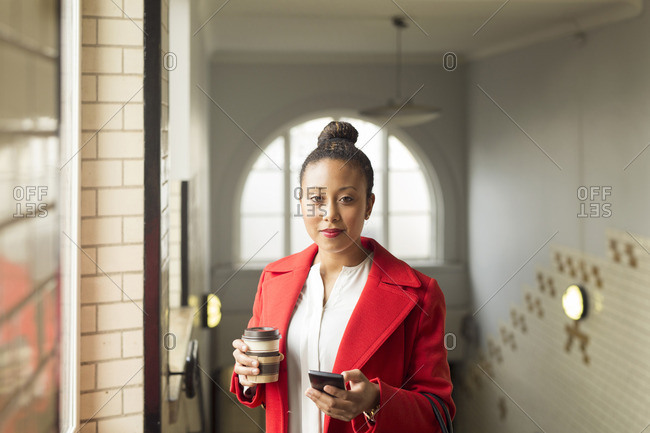 Woman holding coffee and her cell phone