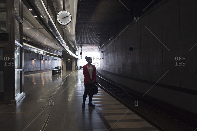 Young woman waiting on a train inside a train station