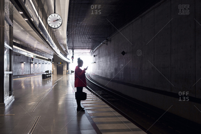 Young woman using cell phone while waiting on a train inside a train station