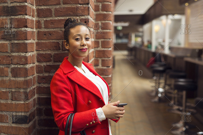 Woman wearing red coat holding a cell phone