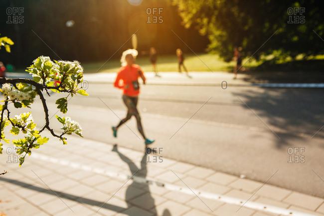 Woman running with baton in a marathon