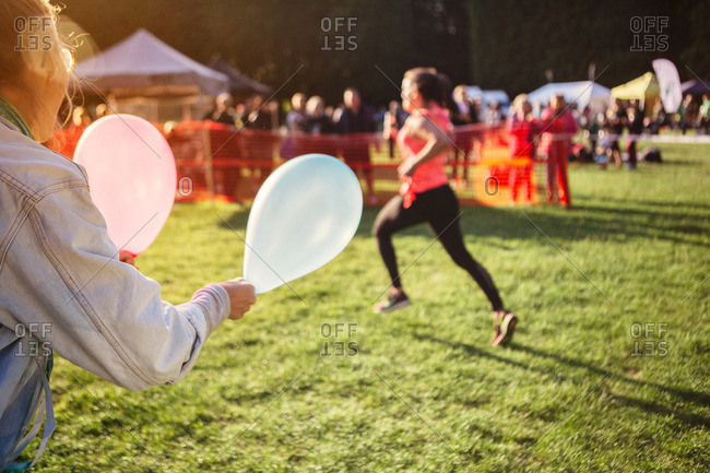 Onlookers wave balloons as marathon runners pass