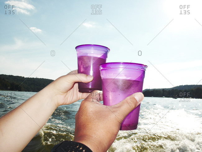 Two hands raising a toast with plastic cups