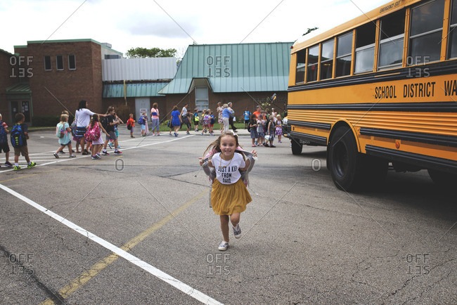 Young girl running across a school parking lot on the last day of school