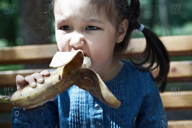 Girl eating a banana outdoors