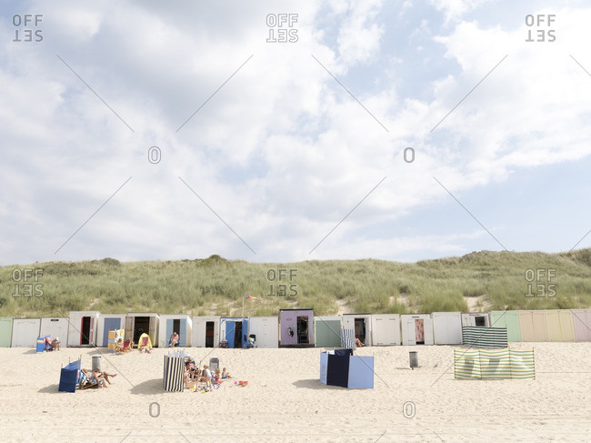 Netherlands - August 18, 2016: People sitting on the beach in front of a row of beach huts in the Netherlands