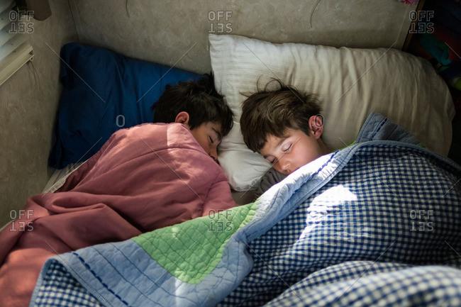 Two teen boys asleep in a bed