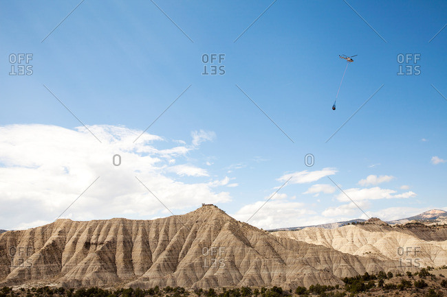 Helicopter flying over remote landscape with net full of gear underneath