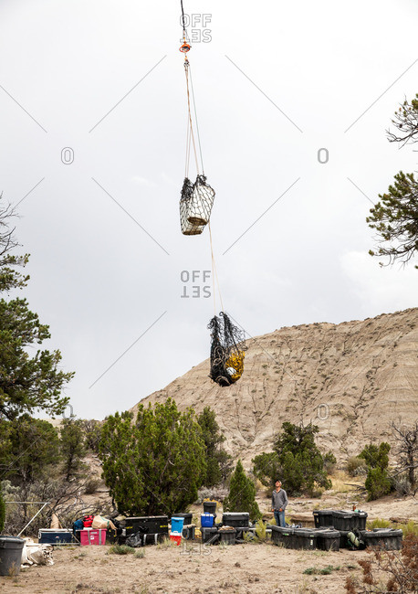 Nets full of gear being dropped by helicopter in remote area