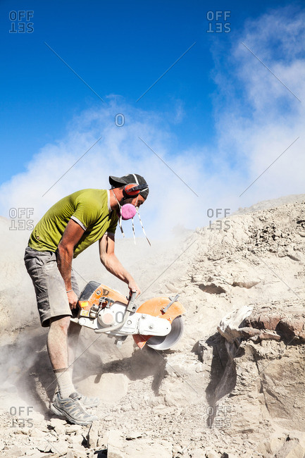 Kaiparowits, Utah, USA - September 20, 2015: A paleontologist using a rock saw while excavating a site in Utah's Kaiparowits Plateau