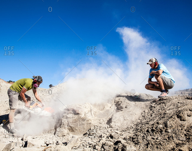 Kaiparowits, Utah, USA - September 20, 2015: Worker watching a paleontologist using a rock saw in the field while excavating a site in Utah's Kaiparowits Plateau