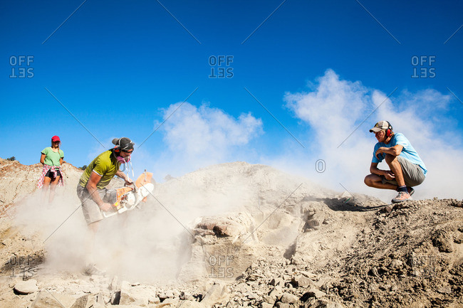 Kaiparowits, Utah, USA - September 20, 2015: Workers watching a paleontologist using a rock saw in the field while excavating a site in Utah's Kaiparowits Plateau