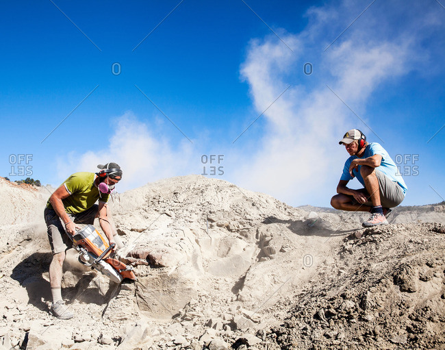 Kaiparowits, Utah, USA - September 20, 2015: Worker onlooking while a paleontologist using a rock saw in the field while excavating a site in Utah's Kaiparowits Plateau