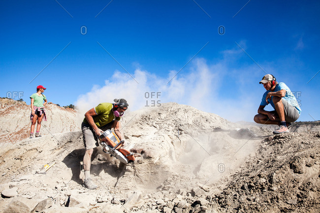 Kaiparowits, Utah, USA - September 20, 2015: Two workers watching a paleontologist using a rock saw in the field while excavating a site in Utah's Kaiparowits Plateau