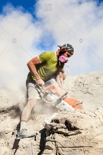 Kaiparowits, Utah, USA - September 20, 2015: Close up of a paleontologist excavating a site with a rock saw in Utah's Kaiparowits Plateau
