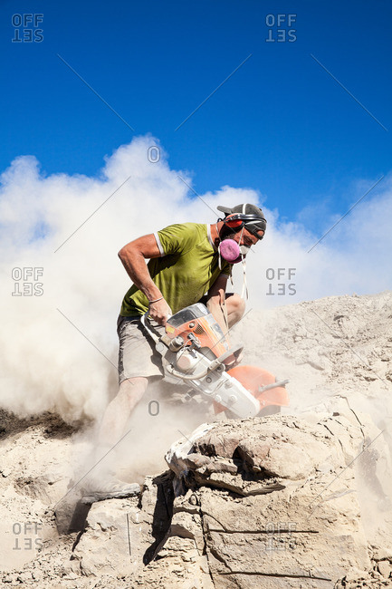 Kaiparowits, Utah, USA - September 20, 2015: A paleontologist excavating a site with a rock saw in Utah's Kaiparowits Plateau