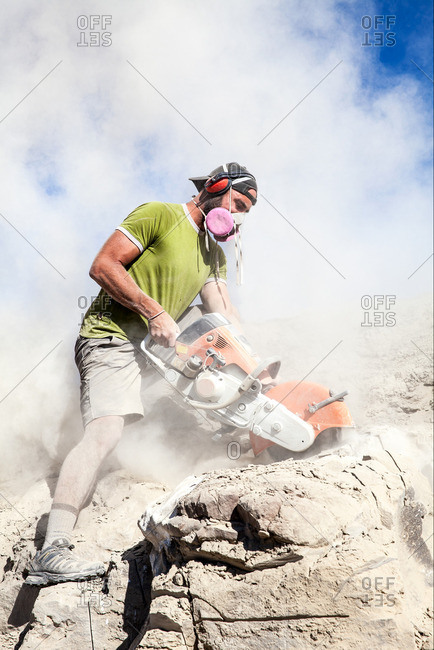 Kaiparowits, Utah, USA - September 20, 2015: Dust surrounding a paleontologist excavating a site with a rock saw in Utah's Kaiparowits Plateau