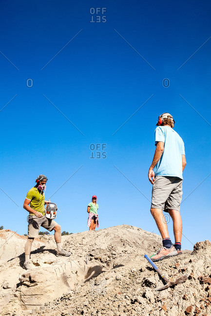 Kaiparowits, Utah, USA - September 20, 2015: Paleontologist with a rock saw in the field with other field workers looking on while excavating a site in Utah's Kaiparowits Plateau