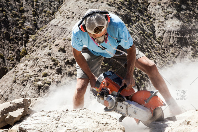 Kaiparowits, Utah, USA - September 20, 2015: Man using a rock saw in the field while excavating a site in Utah's Kaiparowits Plateau