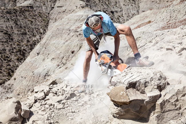 Kaiparowits, Utah, USA - September 20, 2015: Man excavating a site while using a rock saw in the field in Utah's Kaiparowits Plateau