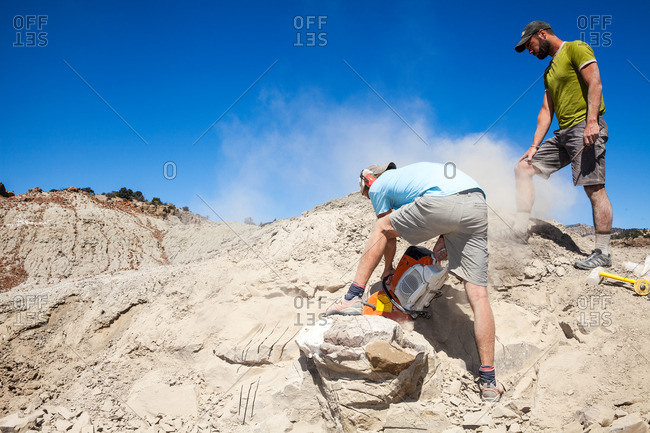 Man looking at a paleontologist using a rock saw in the field to excavate a site in Utah's Kaiparowits Plateau