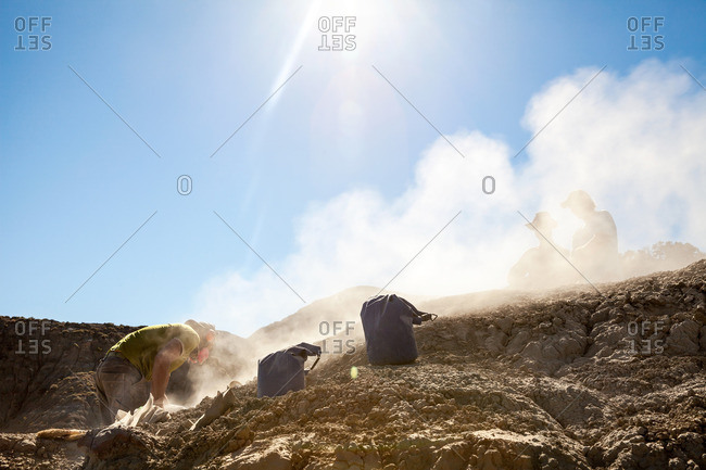 Dust flying while a paleontologist uses a rock saw and two others watch while he excavates a site in Utah's Kaiparowits Plateau