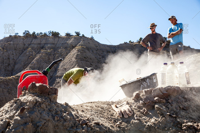 Kaiparowits, Utah, USA - September 20, 2015: Paleontologist using a rock saw while two other paleontologists watch him excavating a site in Utah's Kaiparowits Plateau