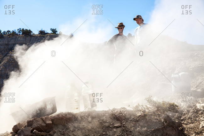 Dust surrounding a paleontologist using a rock saw and two others watch while he excavates a site in Utah's Kaiparowits Plateau