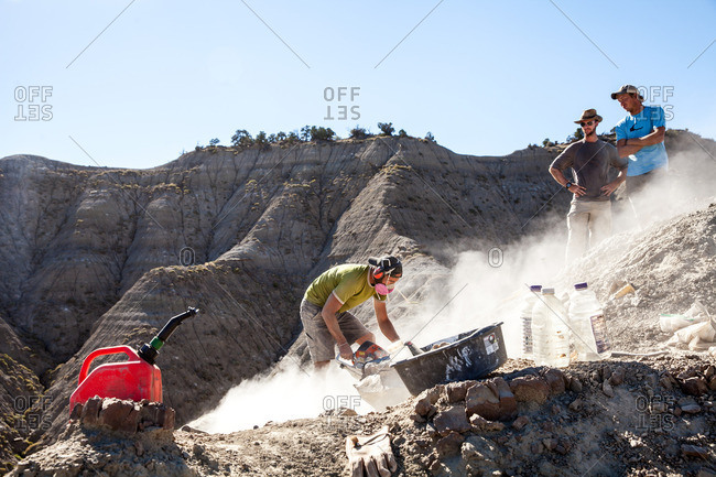 Kaiparowits, Utah, USA - September 20, 2015: A paleontologist using a rock saw in the field while two other paleontologists watch him excavating a site in Utah's Kaiparowits Plateau