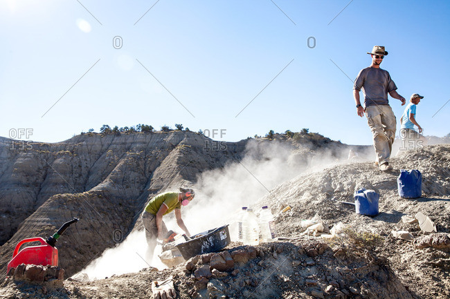 Group of workers on a site while one paleontologist uses a rock saw to excavate in Utah's Kaiparowits Plateau