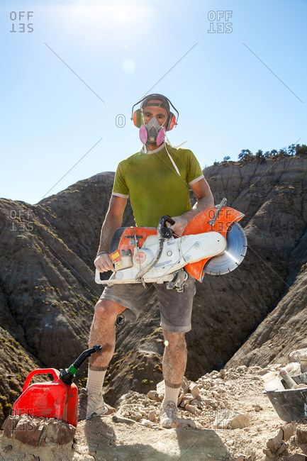 Kaiparowits, Utah, USA - September 20, 2015: Portrait of a paleontologist holding a rock saw in the field during a dig in Utah's Kaiparowits Plateau