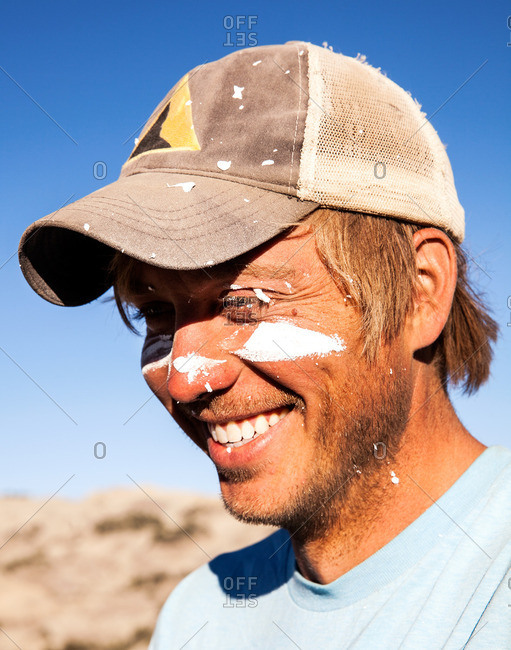 Portrait of a smiling paleontologist with plaster on his face in the field during a dig in Utah's Kaiparowits Plateau