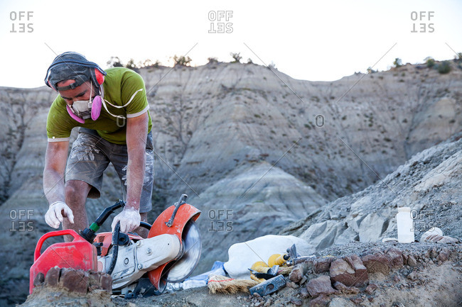 Paleontologist preparing to add gas to a rock saw in the field while excavating a site in Utah's Kaiparowits Plateau