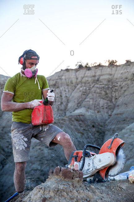 Paleontologist adding gas to a rock saw in the field while excavating a site in Utah's Kaiparowits Plateau