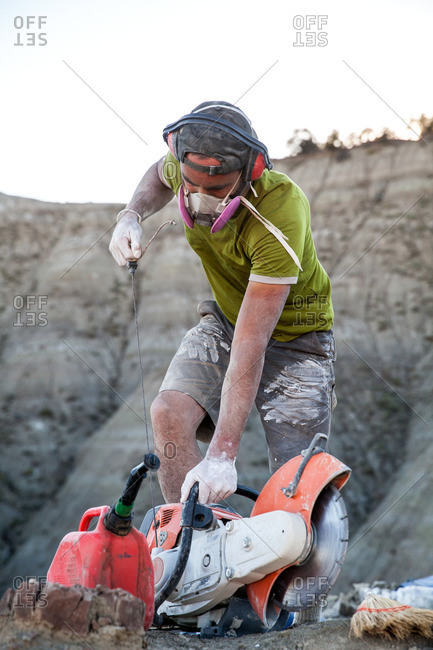 Paleontologist starting a rock saw in the field while excavating a site in Utah's Kaiparowits Plateau