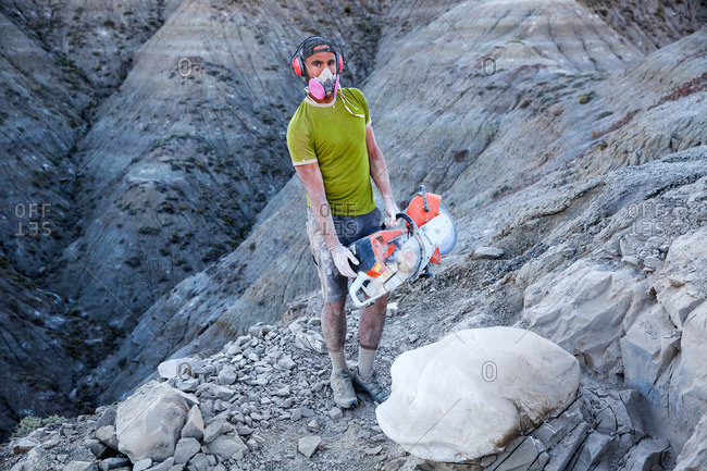 Kaiparowits, Utah, USA - September 20, 2015: Paleontologist holding a rock saw in the field during a dig in Utah's Kaiparowits Plateau