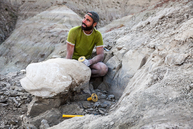Paleontologist using a chisel in the field while excavating a site in Utah's Kaiparowits