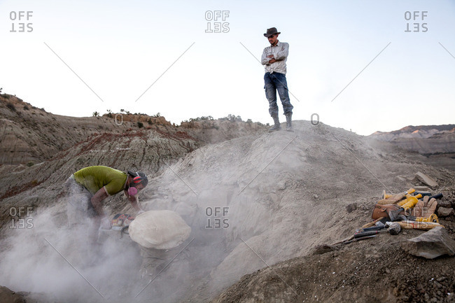 Kaiparowits, Utah, USA - September 20, 2015: A paleontologist using a rock saw in the field while another worker watching him excavating a site in Utah's Kaiparowits Plateau