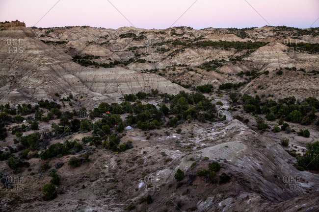 Badlands landscape with set up tents at dawn in Utah's Kaiparowits Plateau