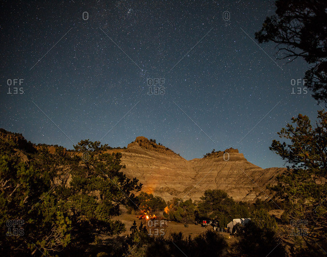 Badlands landscape and campsite under a starry sky in Utah's Kaiparowits Plateau