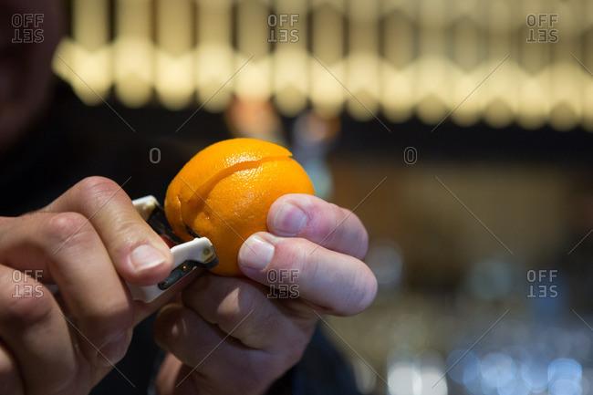 Bartender peeling rind from orange