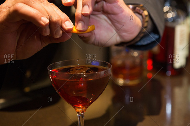 Squeezing oil from orange rind into red cocktail