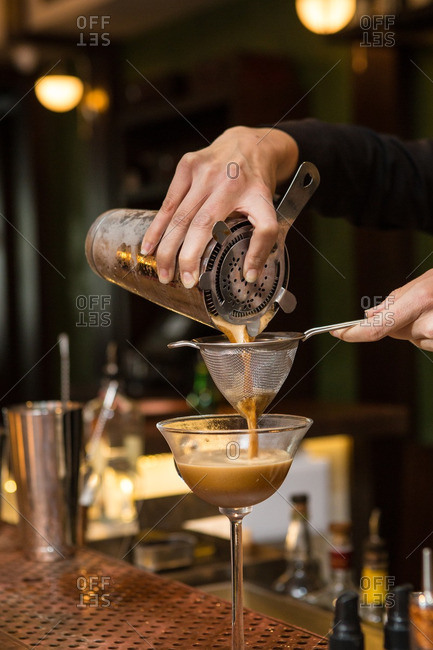 Bartender straining a creamy cocktail into glass