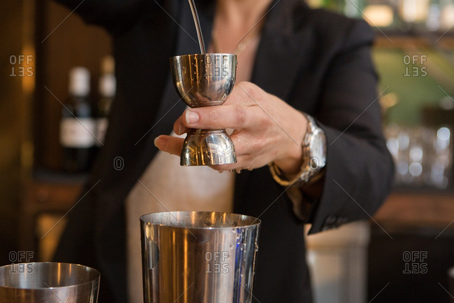 Bartender pouring alcohol into jigger for precise measurement