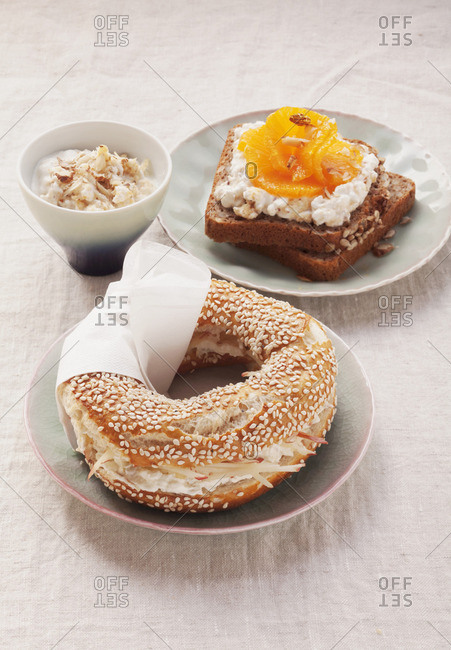 Sesame bagel with cream cheese and grated apple and whole-wheat bread with cottage cheese and oranges
