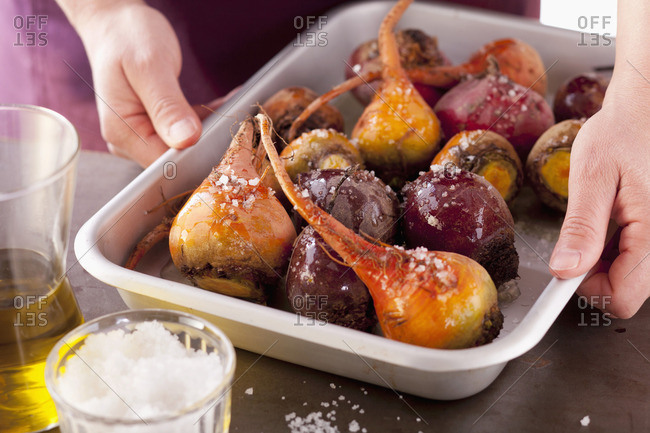 Red and yellow beetroot with salt and olive oil on baking tray