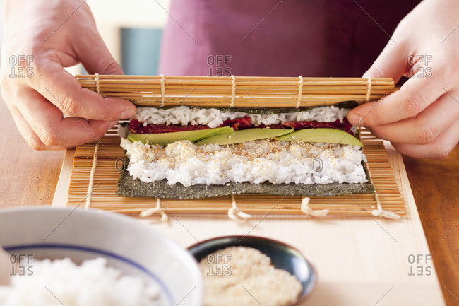 Maki sushi being prepared: a bamboo mat being rolled up