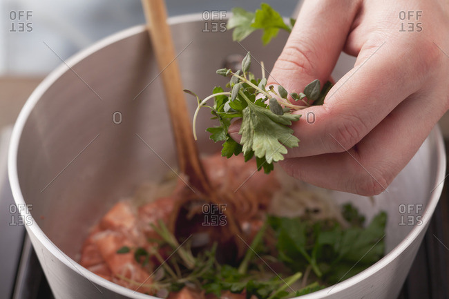 Preparing prawn sauce: add herbs to prawn shells