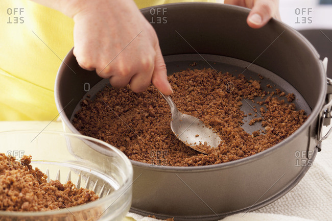 Spreading biscuit mixture on base of a loose-bottomed cake tin